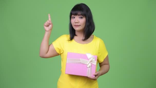 Krásná šťastná Asijské žena drží krabičky při směřující nahoru