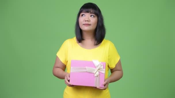 Krásná asijská žena myšlení podržíte-dárková krabička