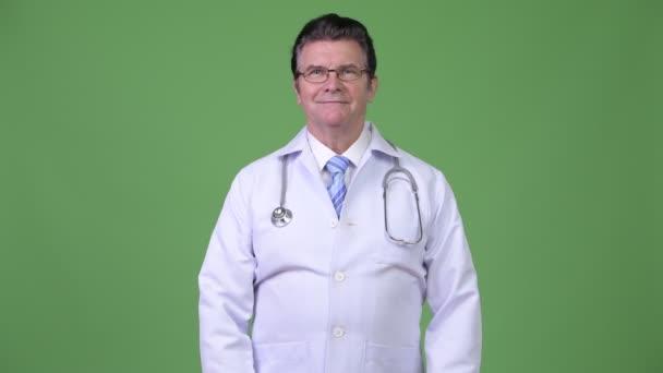 Doktor starší pohledný muž s rukama zkříženýma