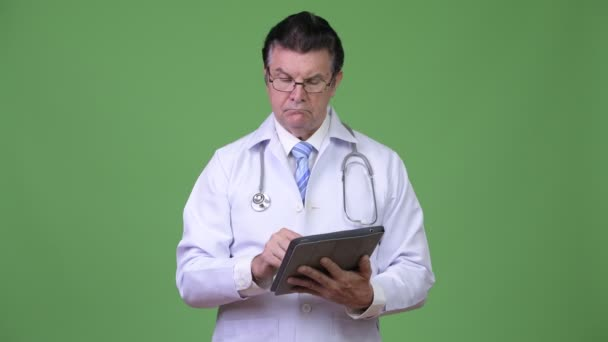 Senior handsome man doctor consulting while using digital tablet