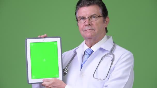 Senior schöner Mann Arzt zeigt digitales Tablet