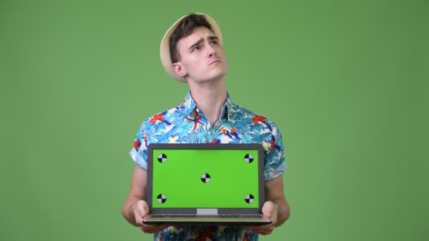 Fiatal jóképű turista ember arra gondolt, miközben bemutatja a laptop