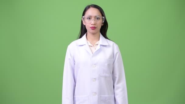 junge schöne asiatische Ärztin mit Schutzbrille