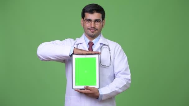 junger hübscher persischer Mann Arzt zeigt digitales Tablet