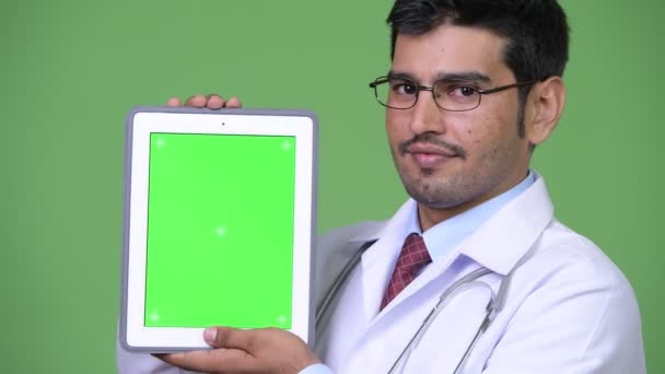 Young handsome Persian man doctor showing digital tablet