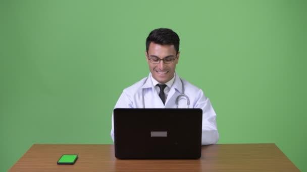 Young handsome Hispanic man doctor against green background