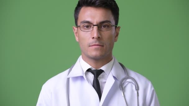 Mladý pohledný hispánské člověčí doktor před zeleným pozadím