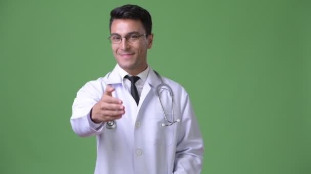 junger hübscher hispanischer Arzt vor grünem Hintergrund