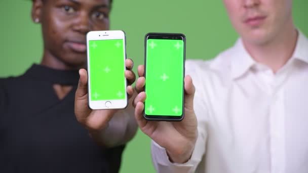 Two young multi-ethnic business couple showing phone together