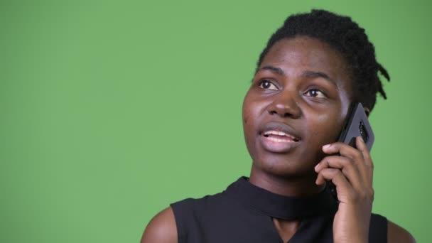 Fiatal gyönyörű afrikai üzletasszony beszél a telefonon