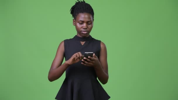 Young beautiful African businesswoman using phone