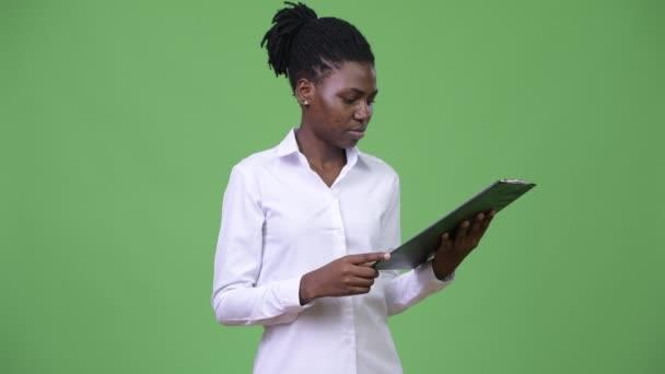 Fiatal gyönyörű afrikai üzletasszony olvasó a vágólapra