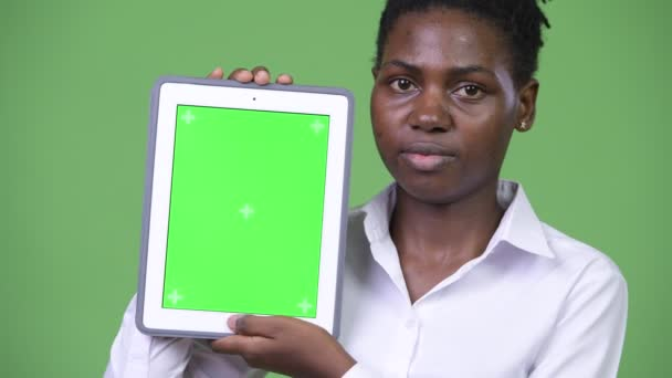 Young beautiful African businesswoman showing digital tablet