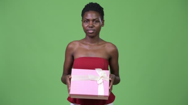 Young happy beautiful African woman holding gift box