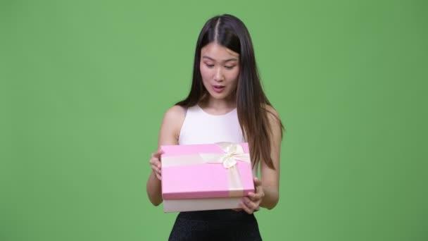 Fiatal gyönyörű ázsiai üzletasszony megnyitása díszdobozban