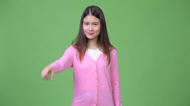 Young beautiful Asian woman pointing at camera