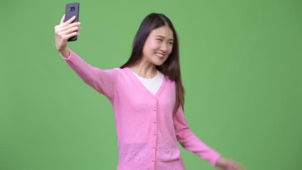 Mladá krásná Asijské žena zobrazeno telefon
