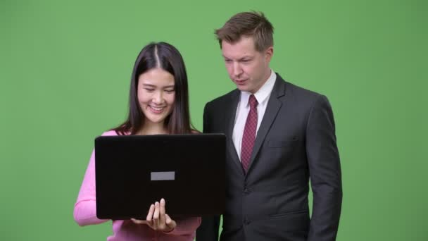 Studio shot of young Asian woman and young businessman together against chroma key with green background