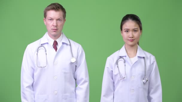 Multi-ethnic couple doctors with arms crossed together