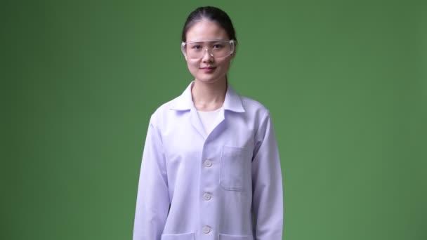 junge schöne asiatische Ärztin mit Schutzbrille lächelt mit verschränkten Armen