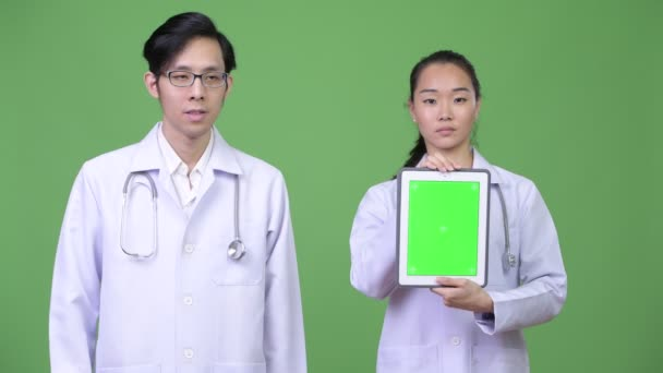 Young Asian couple doctors showing digital tablet together