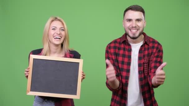 Mladý pár se drží tabuli dává palec nahoru, společně