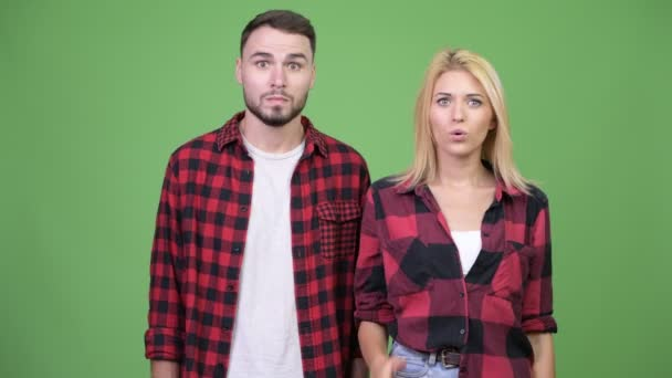 Young woman covering mouth while looking guilty with young man