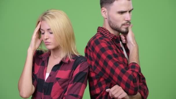 Young stressed couple thinking together with back to back