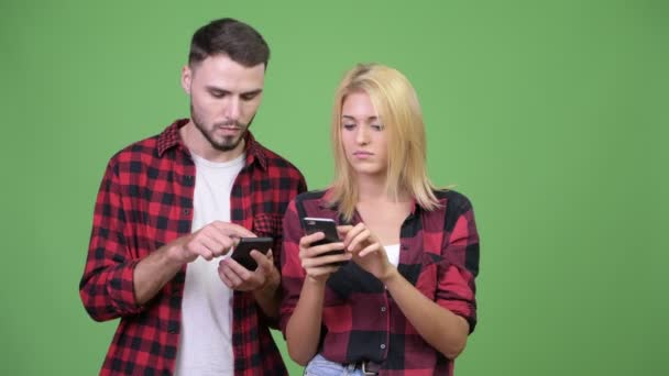 Young couple using phone and getting good news together