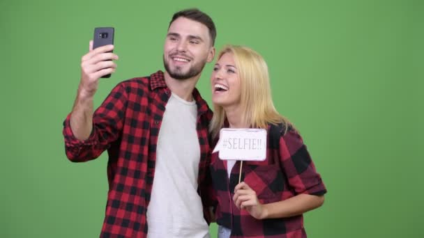 Young couple taking selfie while holding paper sign together