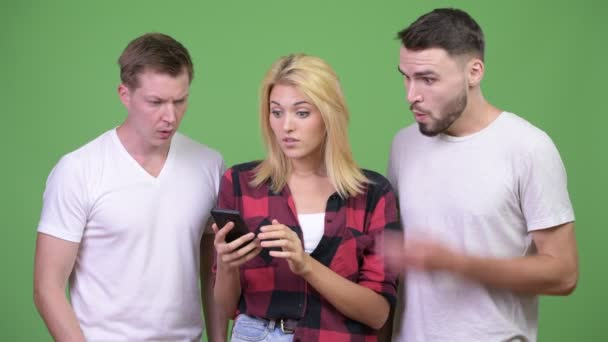 Three young friends using phone together and looking shocked