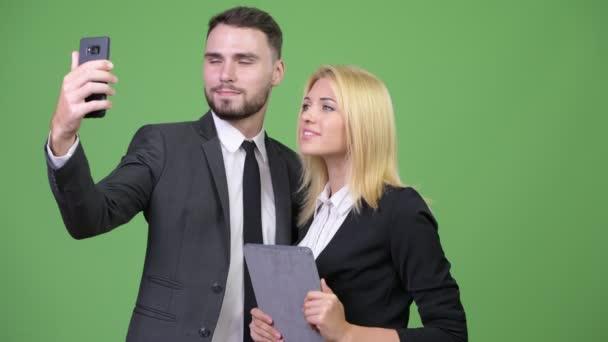 Pár mladých podnikání pomocí digitálních tabletu při pořizování selfie společně