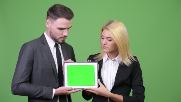 Young happy business couple showing digital tablet together