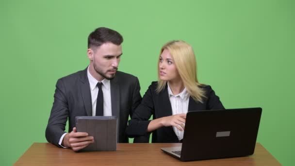 Young happy business couple using laptop together and getting good news