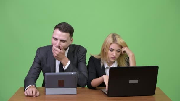 Young business couple looking bored while working together
