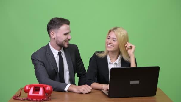 Junger Geschäftsmann flirten mit jungen geschäftsfrau und wütend am Telefon