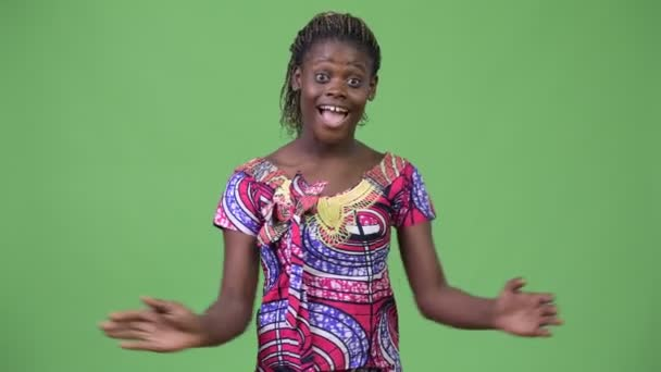 Studio shot of young African woman wearing traditional clothes against chroma key with green background