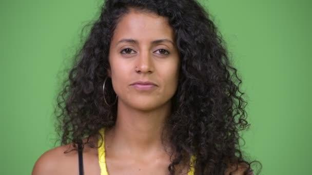 Stúdió lövés a fiatal gyönyörű spanyol nő, göndör haj ellen zöld háttér chroma-kulcs