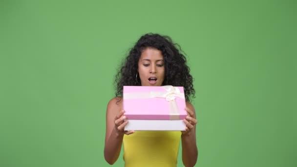 Mladá krásná žena hispánský pohledu překvapen při otevírání krabičky