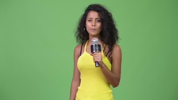 Young beautiful Hispanic woman using microphone
