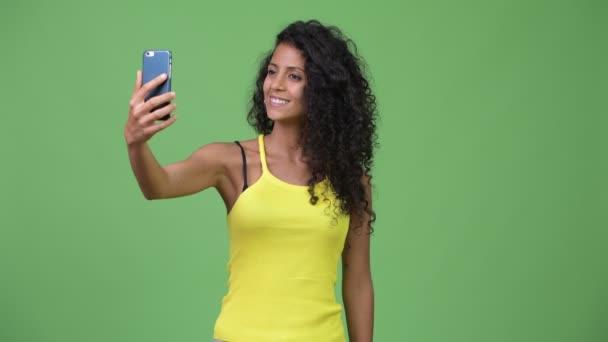 Young beautiful Hispanic woman taking selfie