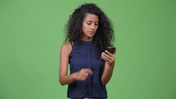 Studio záběr Mladá krásná hispánské podnikatelka s kudrnatými vlasy proti chroma klíč se zeleným pozadím