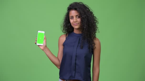 Young beautiful Hispanic businesswoman showing phone