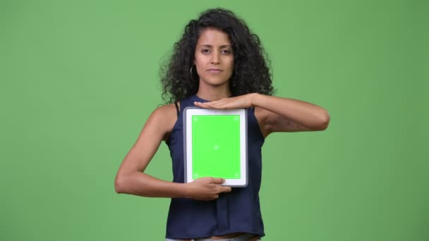 Young beautiful Hispanic businesswoman showing digital tablet