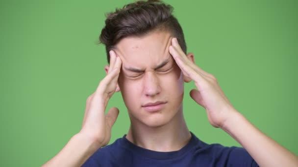 Young handsome teenage boy having headache