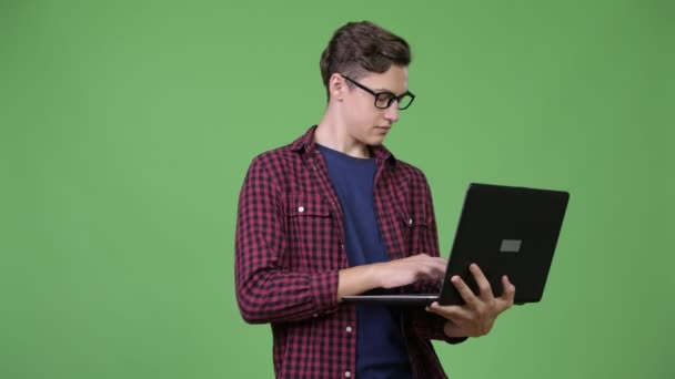 Young handsome teenage nerd boy using laptop