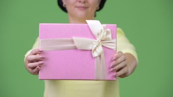 glückliche Geschäftsfrau lächelt, während sie Geschenkbox schenkt