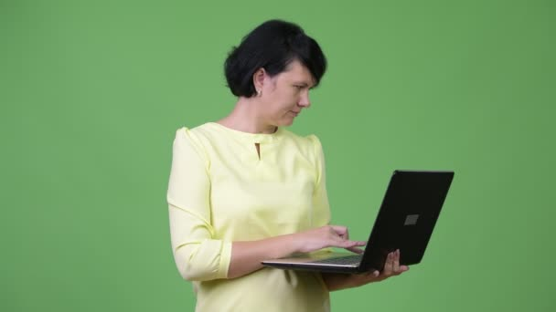 Beautiful businesswoman with short hair using laptop