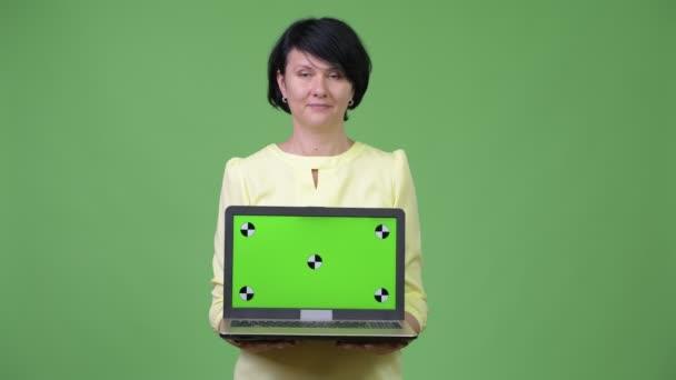 Krásná obchodnice s krátkými vlasy ukazuje notebook při pohledu šokován