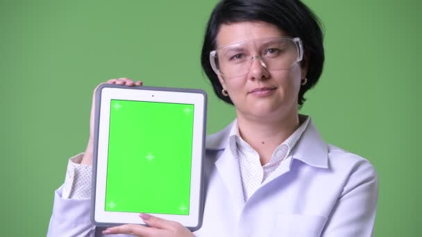 Krásná žena lékař nosit ochranné brýle a zobrazení digitální tabletu